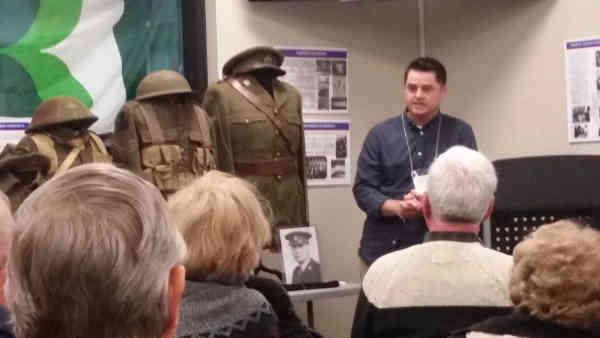 bill speaking, uniforms on display